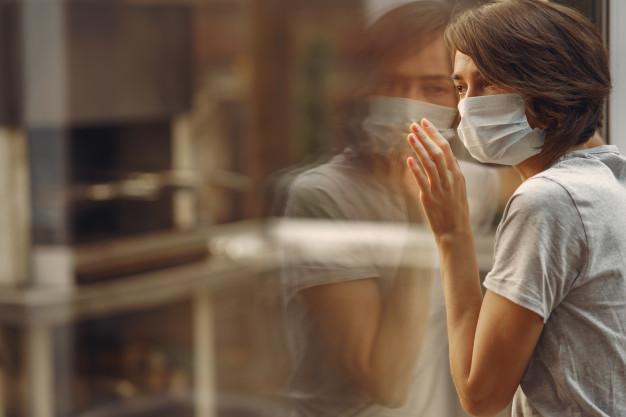 девушка в маске у окна